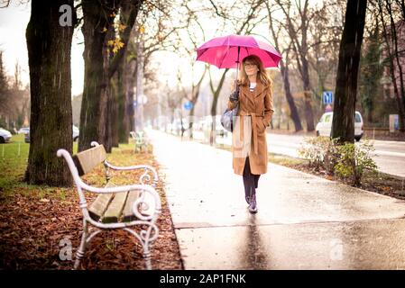 Full length shot of mature woman holding umbrella while walking on the street on a rainy day. - Stock Photo