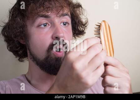 Portrait of a young guy with long dirty hair and problematic scalp. Holding a comb with lost hair, looking at her indignantly. Hair loss at an early a - Stock Photo