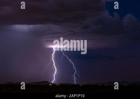 Vivid lightning bolts strike a mountain as a powerful monsoon thunderstorm drifts across the desert near Tonopah, Arizona. Stock Photo