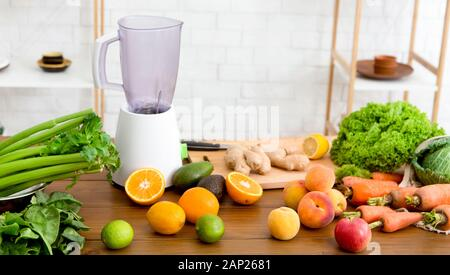 Blender jar and fresh fruits and vegetables on table at home - Stock Photo