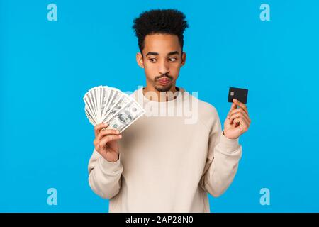 Indecisive and troubled young african-american guy facing tough decision, pouting, exhale hard making choice, holding money and credit card, consider - Stock Photo