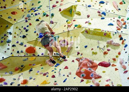 Free climber child young boy practicing on artificial boulders in gym, bouldering