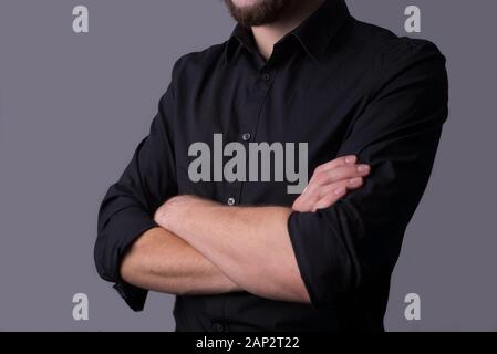 A man in a black jacket, on a dark gray background. minimalistic concept. Empty free space. Portrait of a young guy in a black business suit, holding - Stock Photo