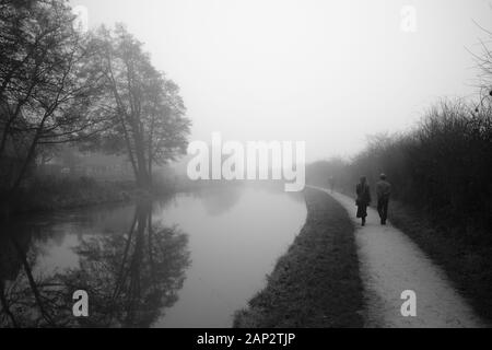 Early misty morning by the Trent and Mersey canal (Staffordshire,UK). Couple walks on the footpath that goes in to eternity - Stock Photo