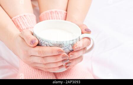 Female hands envelop a cup on a sofa early in the morning - Stock Photo