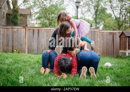 Two adult brothers build a human pyramid with their children outside - Stock Photo