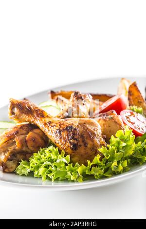 Roasted chicken legs with lettuce salad potatoes and tomatoes isolated on white