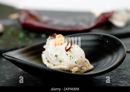 close up of a plate of cod fish accompanied by fried garlic and small chili pepper and cod skin served on slate trey, typical Spanish ingredients. - Stock Photo