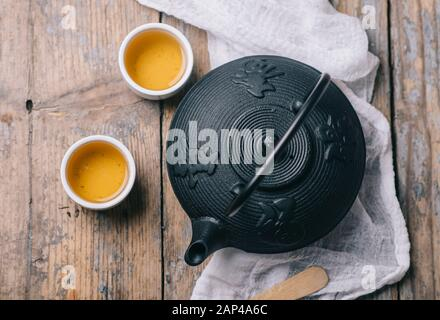 Traditional japanese herbal tea recipe prepared in cast iron teapot with organic dry herbs from above. Top view of asian traditional hot beverage on w - Stock Photo