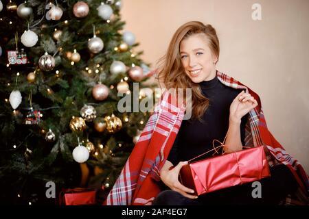 Beautiful blue-eyed girl sitting on floor near Christmas tree, open gift - Stock Photo