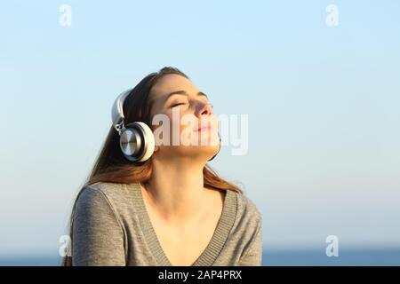 Relaxed woman wearing headphones meditating listening to music on the beach at sunset