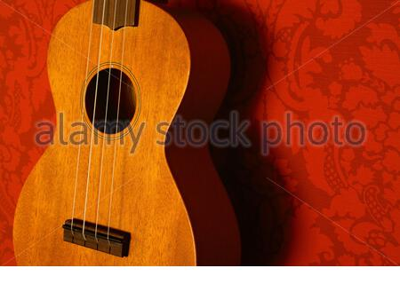 Close-up of a ukulele with honey-coloured wood against a red wallpaper background
