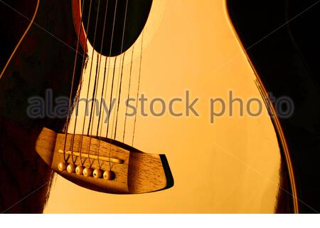 Close-up of an electro acoustic guitar reflecting golden light - Stock Photo