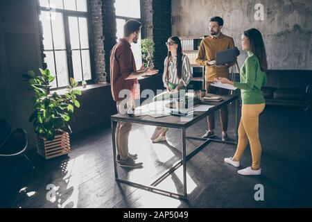 Company of four nice successful skilled qualified intelligent people leaders professional IT specialists HR recruiters discussing agenda at industrial - Stock Photo
