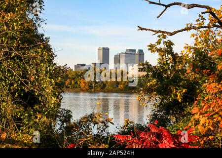 Scenic  landscape view of downtown Tulsa from the west bank of the Arkansas river through the trees. - Stock Photo
