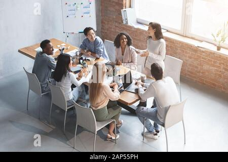 Enthusiastic girl sharing her ideas with cheerful colleagues while meeting