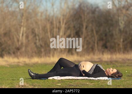 Pregnant woman resting on her back on the grass lawn sunbathing her bare belly under a warm winter sunshine. - Stock Photo