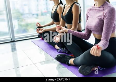 Three young women meditating in lotus pose during yoga class in health club. Women sitting on floor near window with city view - Stock Photo