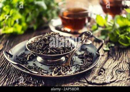 Dried tea leaves in bowl on rustic wooden table - Stock Photo