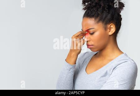 Sad young woman touching her nose bridge