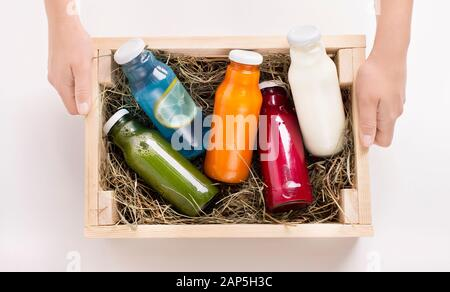 Female holding wooden box with Different flavoured detox drinks - Stock Photo