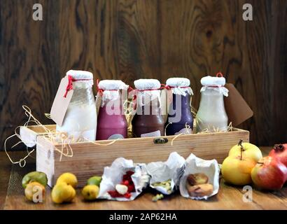 colorful Smoothies at the bottles. Colorful drink, milk shake in bottle with fresh vegetables and superfoods on a wooden background. Healthy, clean - Stock Photo