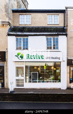 A recently opened shop specialising in the sale of CBD products with a workman on scaffolding the opposite side of the road reflected in the window - Stock Photo