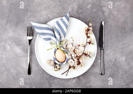 Beautiful Easter table setting with egg in napkin Easter Bunny and blossoming branches on stone background. Top view. - Stock Photo