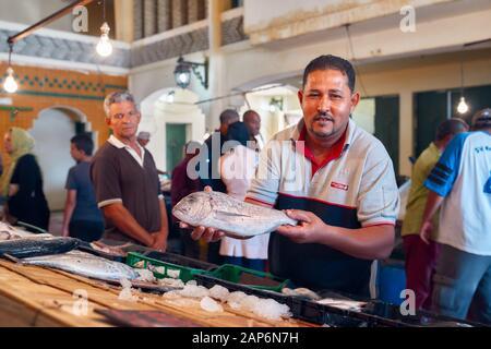 Tunisia, October 10/2019 Traditional Tunisian fish market, fishmonger shows fresh fish for sale - Stock Photo