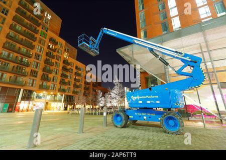 A boom lift (cherrypicker) parked in Granary Wharf in Leeds used for working at heights, such as cleaning windows on high buildings - Stock Photo