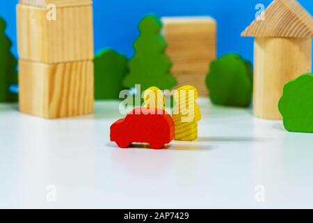 Insurance or business concept. Wooden persons with a car on the street of City with wooden blocks houses on the background.. Miniature people - Stock Photo