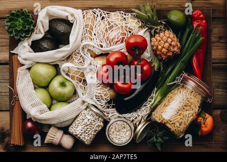 Zero waste food shopping. Fruit and vegetables in cotton bags, pasta, cereals and legumes in glass jars, herbs and spices on wooden background. Health - Stock Photo
