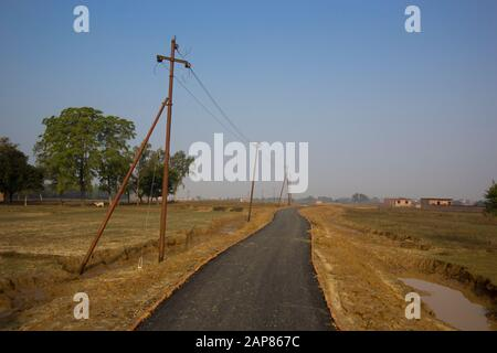 A look down a single lane, paved rural road with a line of humble, rusty poles for power lines. In Allalabad, Uttar Pradesh, India. - Stock Photo