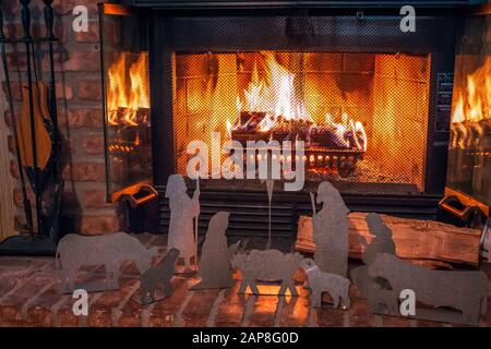 Metal nativity scene in front of a lit fireplace during Christmas time - Stock Photo