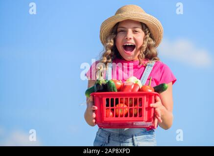 Selling homegrown food concept. Natural vitamin nutrition. Vegetables market. Organic vegetables. Girl cute child farming. Gathering vegetables in basket. Village rustic style. Sunny day at farm. - Stock Photo
