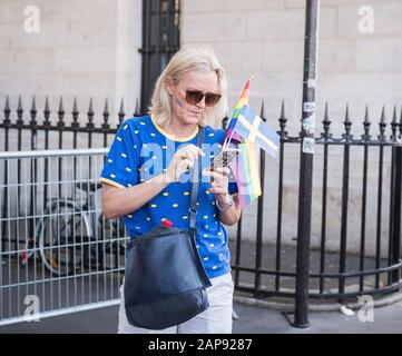June 29 2019, Paris, France. Gay Pride Parade Day. Beautiful close up shot of a woman in her fifties looking at her phone. She has rainbow paint on - Stock Photo