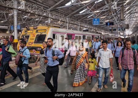 Commuters at Chhatrapati Shivaji Maharaj Terminus in Mumbai, India, disembarking from a suburban train