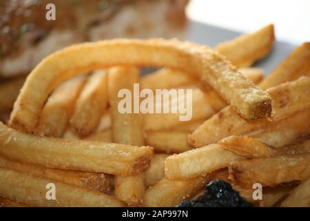 fresh potato string or straight cut french fries oven baked or deep fried as the perfect side dish at any restaurant for dine in or take out orders - Stock Photo