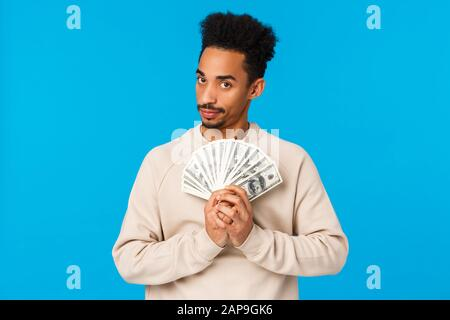 Guy got cash, thinking what buy, how waste money during winter holidays sale season. African american good-looking man with afro haircut holding - Stock Photo