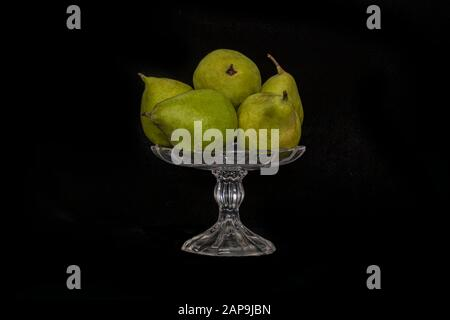 Still life. Ripe pears in a glass vase on a black background close up - Stock Photo