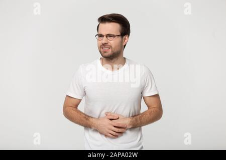 Unhealthy young man feeling pain in stomach, studio portrait. - Stock Photo