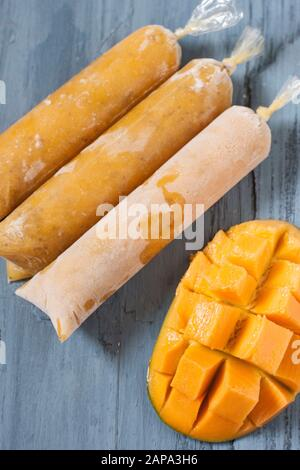 Three mango chia lollies on blue background with a mango cut in half - Stock Photo