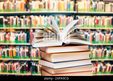 Opened book on a pile in front of a large bookshelf - Stock Photo
