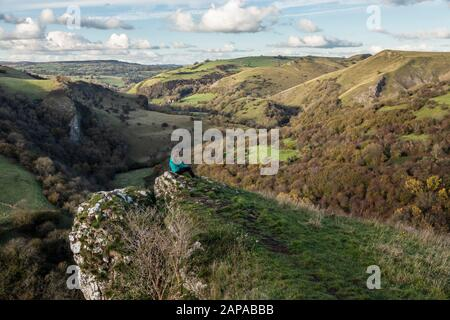 Young woman looking at the view over the Manifold Valley, near Wetton, Peak District National Park, Staffordshire - Stock Photo