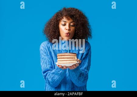 Cute and tender, young african-american woman with curly haircut, in sweater, holding b-day cake, blow-out candle and make wish to come true - Stock Photo