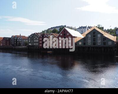 Wooden buildings reflected in water at Nidelva river in european Trondheim city at Trondelag district in Norway