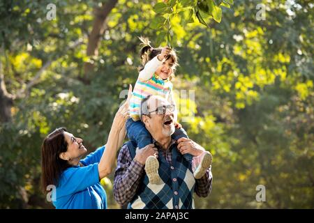 Grandmother with granddaughter sitting on grandfather's shoulder at park