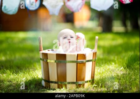 little girl plays with foam in a wooden bath in the backyard - Stock Photo