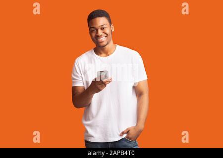Smiling black man using cell phone looking at camera - Stock Photo