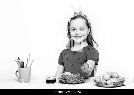small baby girl or cute child with happy face in purple dress holding and showing red easter egg isolated on white background - Stock Photo